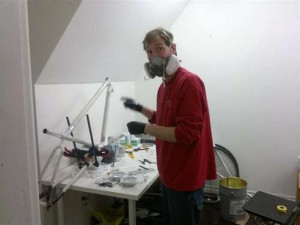 andrew working wearing a respirator and working on his aluminum bike
